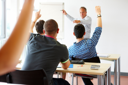 mature teacher in classroom with eager students waiting to answer his question