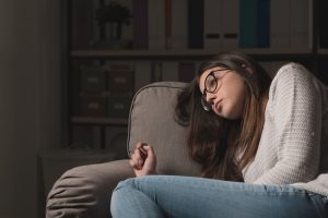 74152067 - sad young woman with glasses sitting on the couch at home, she is depressed and lonely