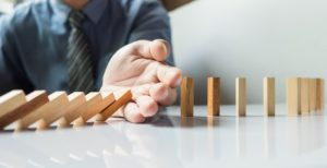 businessman-hand-stop-dominoes-continuous-toppled-risk-with-copyspace_1423-18