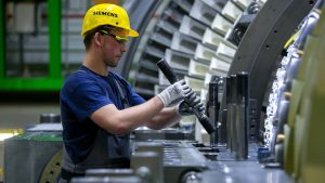 An employee checks a bolt component fitting on a H-class turbine on the assembly line of Siemens AG's gas turbine factory, in Berlin, Germany, on Tuesday, Feb. 2, 2016. Siemens, Europe's largest engineering company, criticized the U.K. government for creating uncertainty in the energy industry, saying it hampers investment in gas plants, wind farms and factories. Photographer: Krisztian Bocsi/Bloomberg