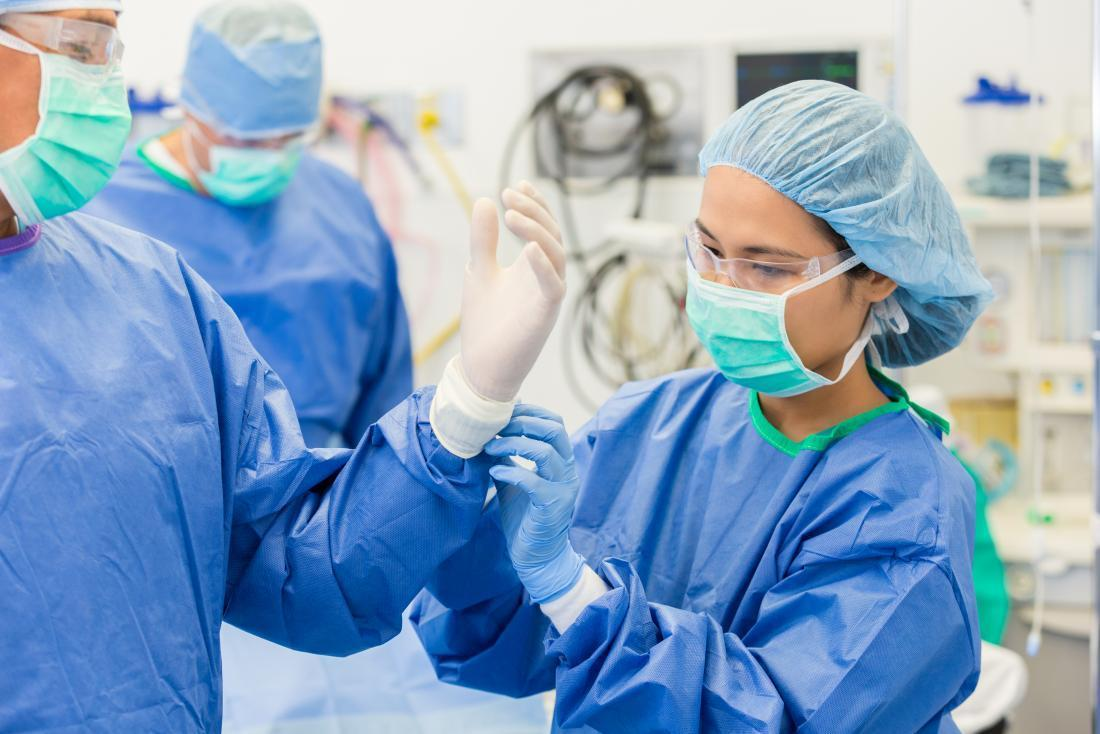 surgeon-wearing-mask-protective-eyewear-hair-net-gown-and-helping-other-surgeon-with-sterile-gloves-before-operation